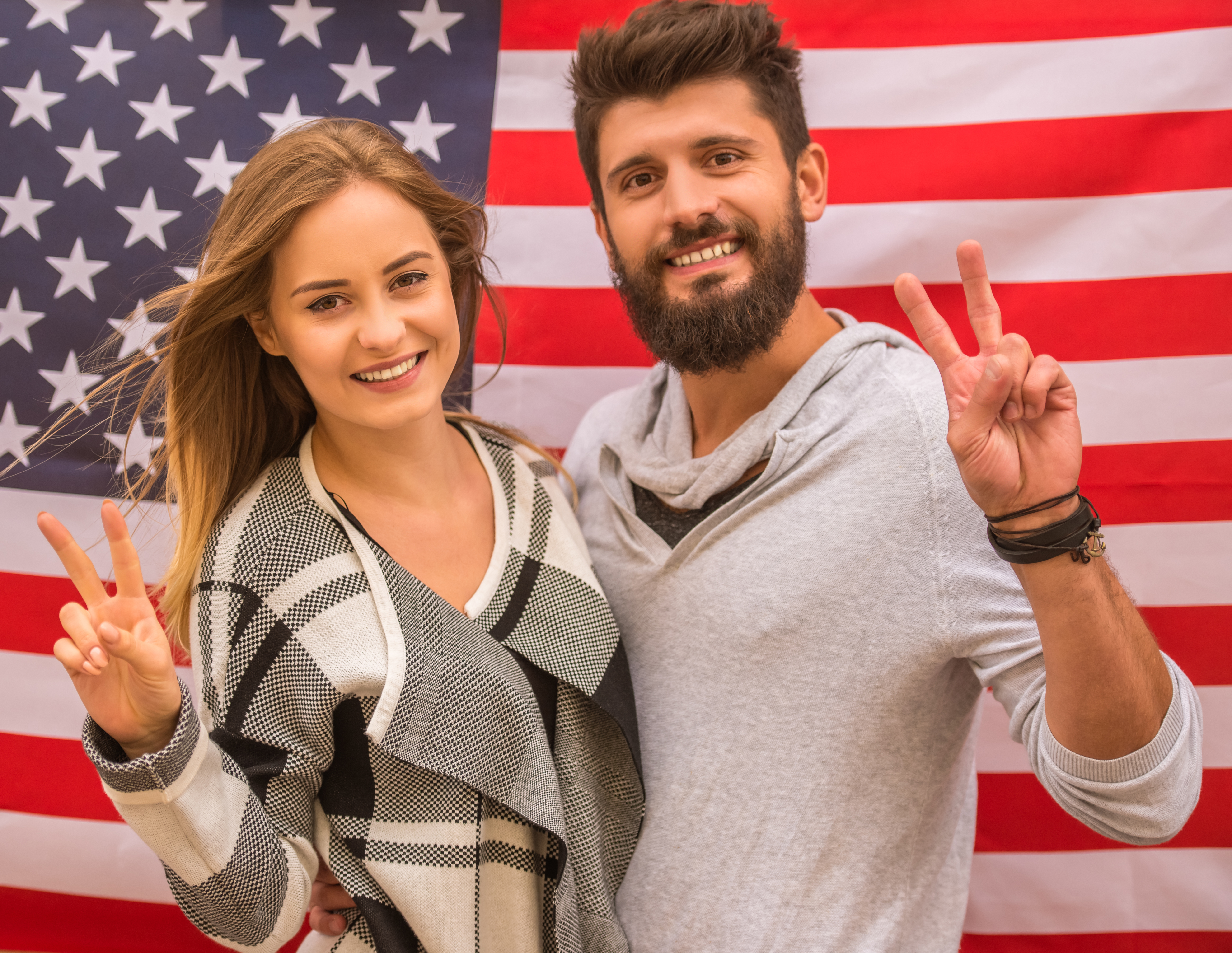 Portrait of a young happy couple on the background of the US flag